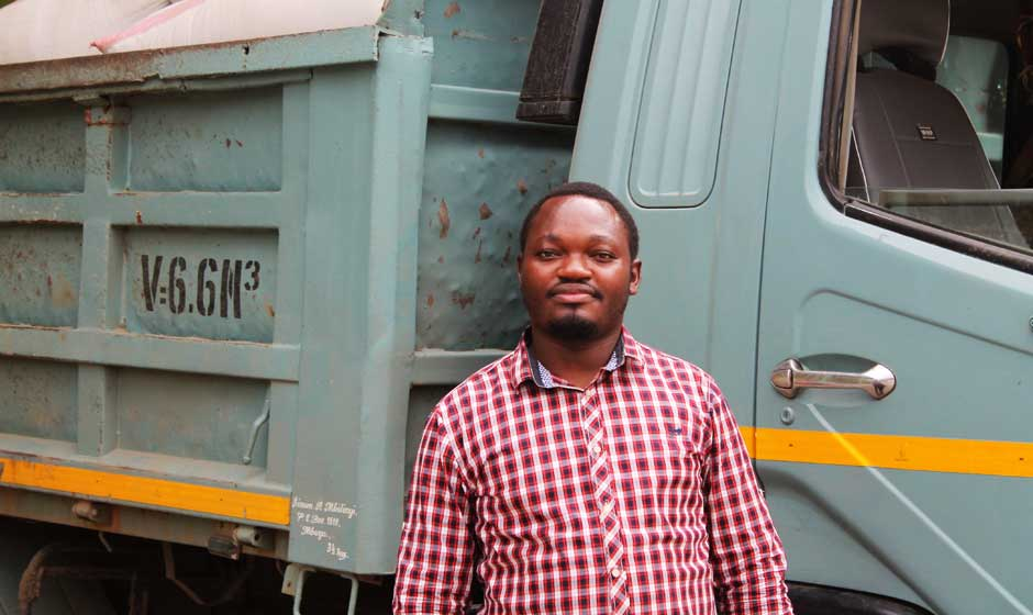 Lazaro Mwakipesile, General Manager of the Raphael Group, in front of the truck used to transport the processed products to his market partners